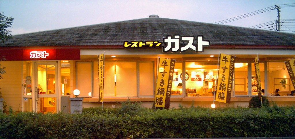This image shows a famiresu. It features yellow flags outside. Inside, people can be seen sitting at tables.
