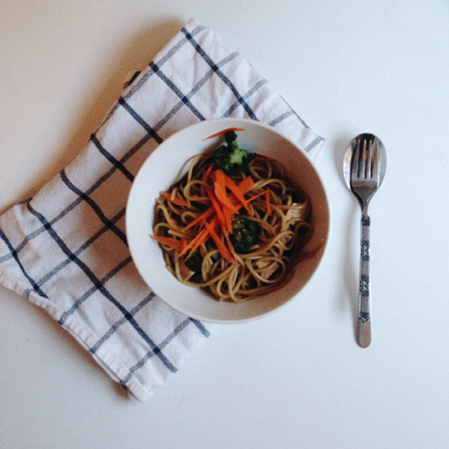 the finished pasta meal in a bowl, set on a white and blue napkin with a fork beside them