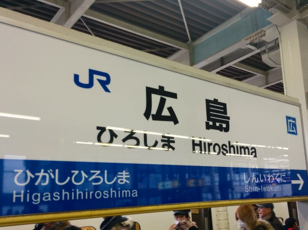 "This image shows a signboard featuring the text, ""Hiroshima."" It is at Hiroshima station."