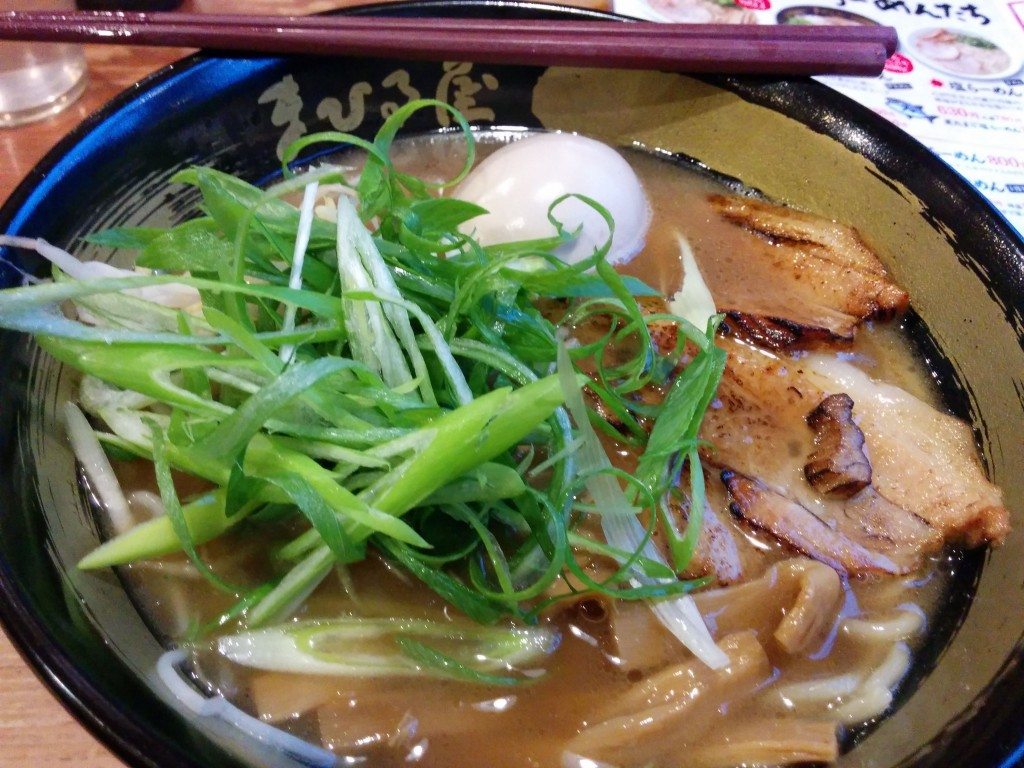 This image shows a bowl of ramen featuring pork, an egg, and vegetables.