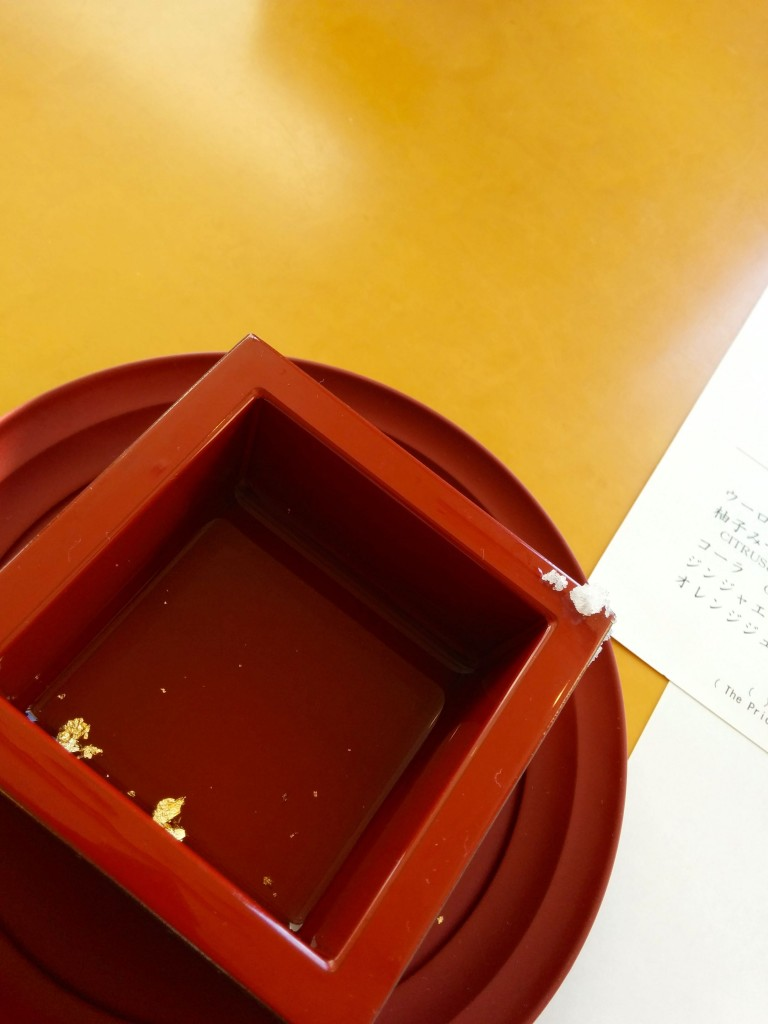 This image shows a cube-shaped cup with sake inside. Flakes of gold can be seen inside the sake.