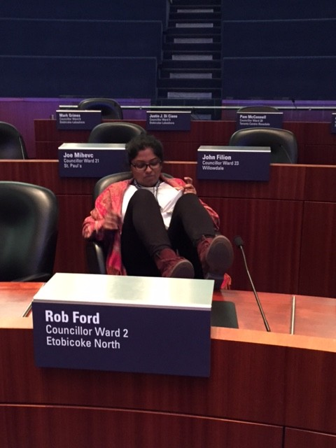 Picture of Api sitting in Rob Ford's seat in city council chamber.