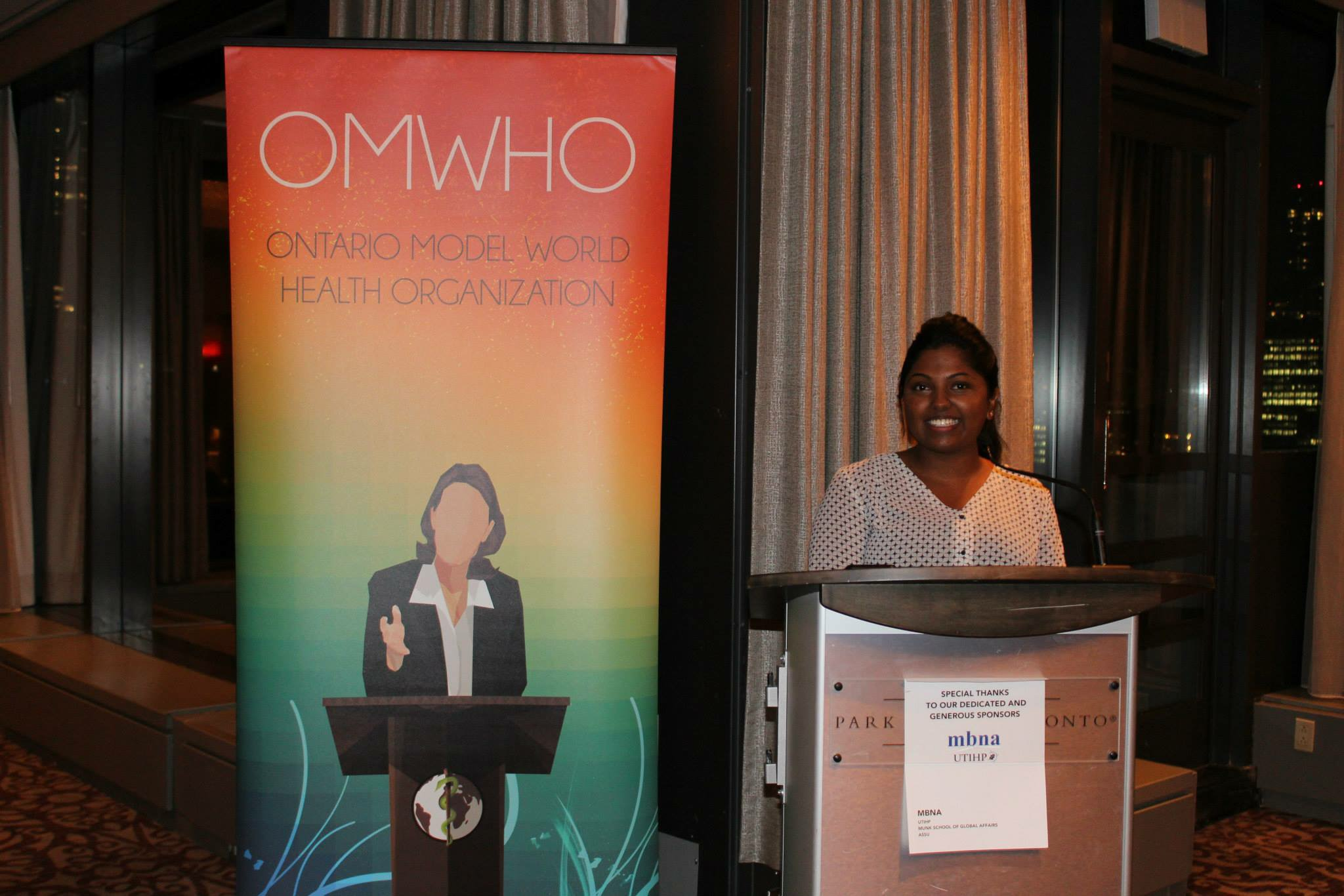 "Api standing behind podium with standing banner next to her reading ""Ontario Model World Health Organization"""