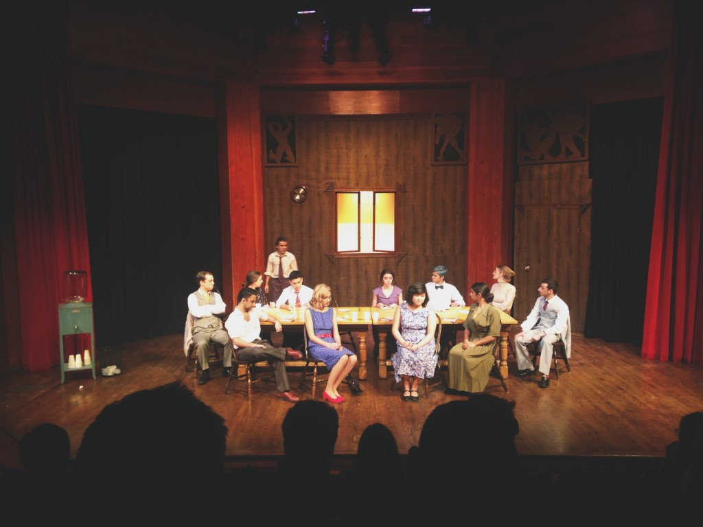 a picture of the performance happening on stage. The 12 characters are sitting in chairs around a large table - on character is standing up addressing the group.