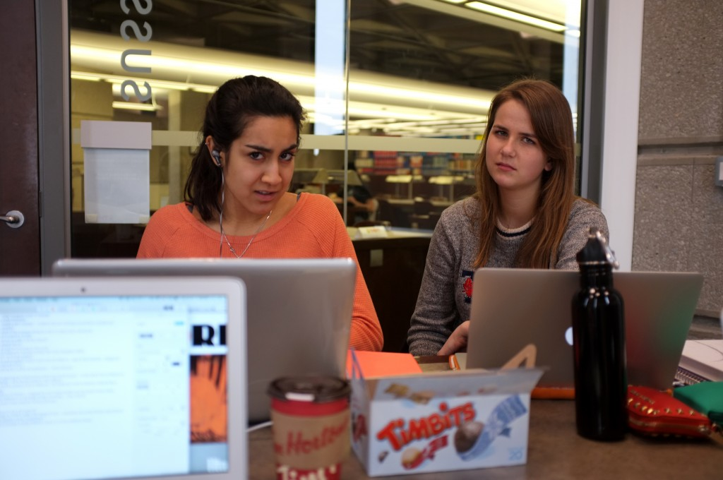 a table at Robarts, in the foreground is a laptop, in the background in focus are two girls looking very judgementally at the camera. They also have laptops. On the table are timbits, water bottles, a pencil case, and a tim hortons coffee cup.