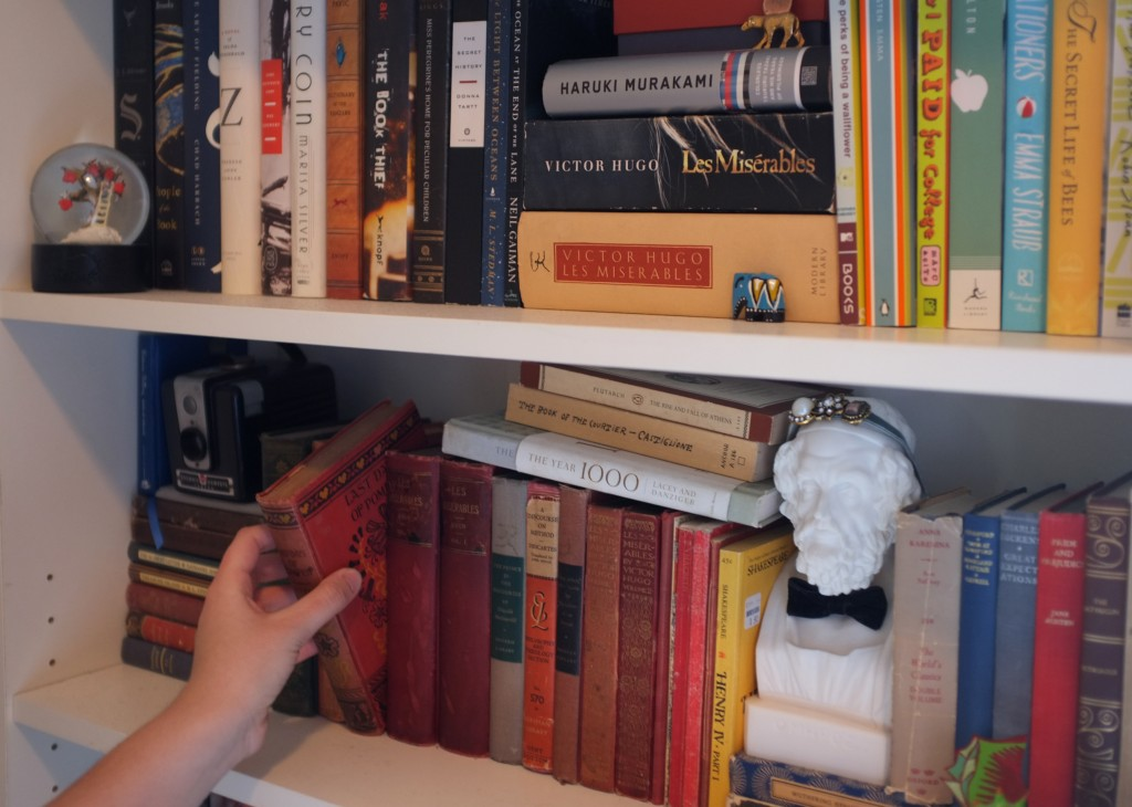 two rows of a bookshelf. The bottom row has old books that are mostly bound in reddish binding and a bust of homer wearing a velvet bowtie. The top shelf has more modern books.