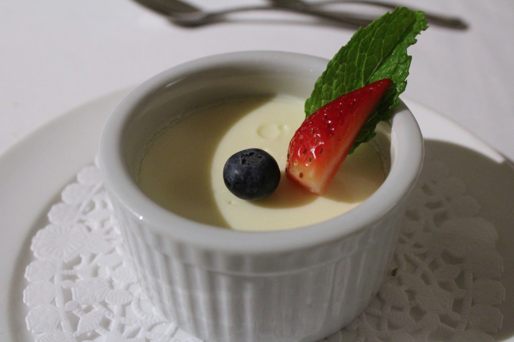 Photo of a cream dessert in a white bowl with a fruit garnish