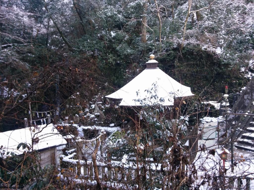 This image shows a small, snow-covered Shinto shrine. It features a pointed roof with a gold ornament on top.