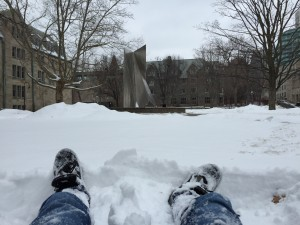 My feet, lying in the snow, looking at an odd statue in a park behind the residences of Saint Michael's College