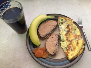A fried omelette, with marble rye peanut butter toast, a banana, and dried apricots next to a glass of coke zero