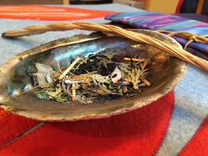 A large abalone shell with sage, cedar, and sweetgrass