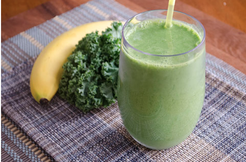 picture of a glass of kale smoothie with banana and kale leaves on the side