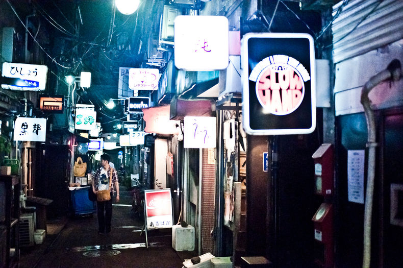 This image shows a narrow street lined with neon signs. It is part of a street in Shinjuku District's Golden-Gai area.