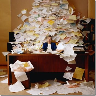 Photo of woman buried under stacks of paper with a general look of anguish and despair playing across her downtrodden face.