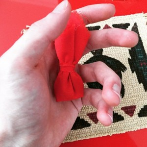 My hand, holding a small red tobacco bag, with a turtle image peeking in from the background