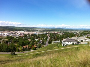 A huge view of the green foothills and a small town in a valley, with the Rocky Mountains in the background