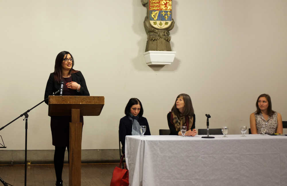 a woman stands at a podium speaking while three other women look on from their positions behind a table