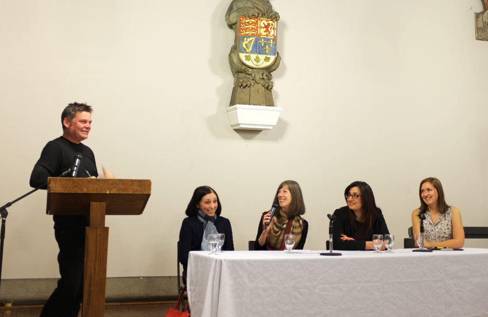 a man stands behind a podium and addresses the four women sitting behind a table