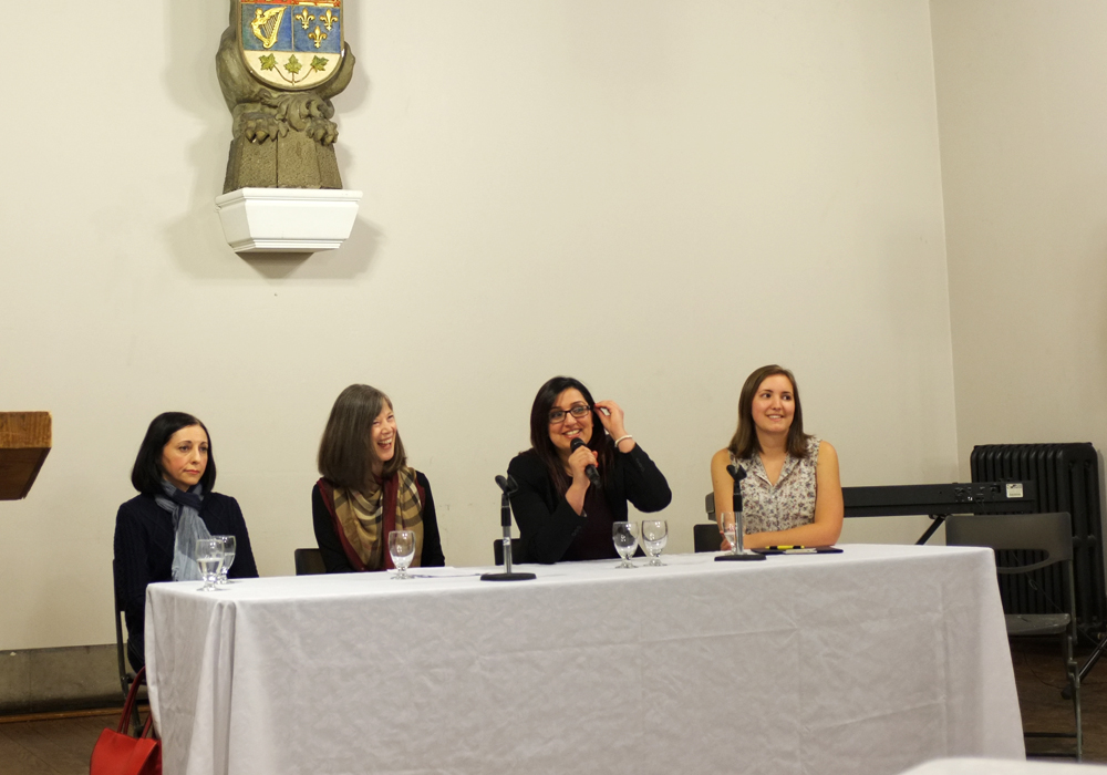 four women sit behind a table, one speaks into a microphone while the other three look on