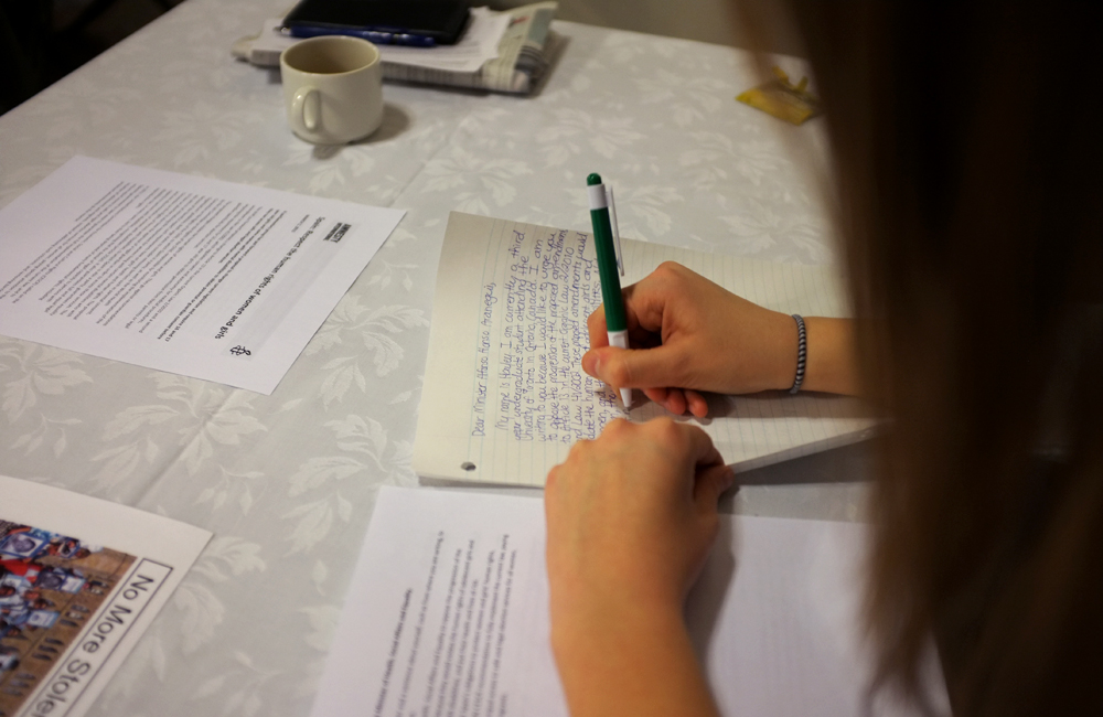 a person writes a letter on a lined peace of paper