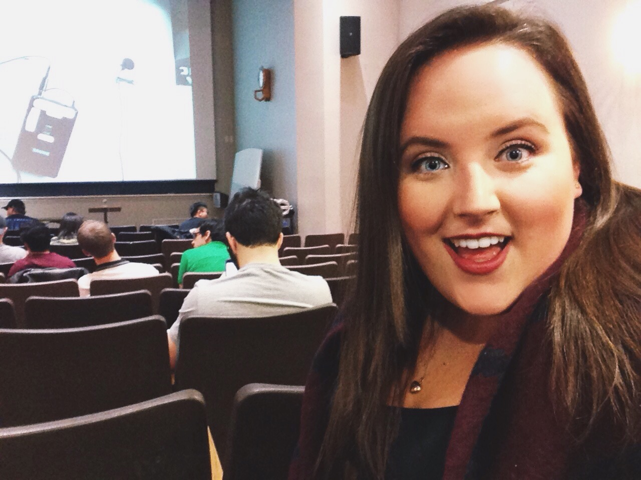 A selfie of me in the lecture hall, smiling at the lecture screen, acting goofy