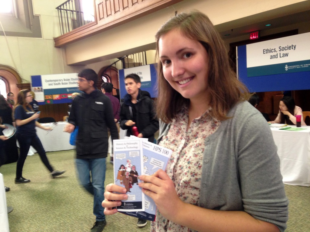 a girl holds up flyers for history and philosophy of science and smiles.