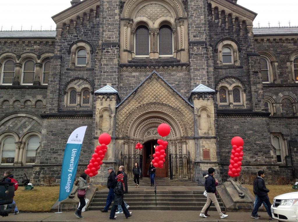 the front of the main university college building flanked by red balloons