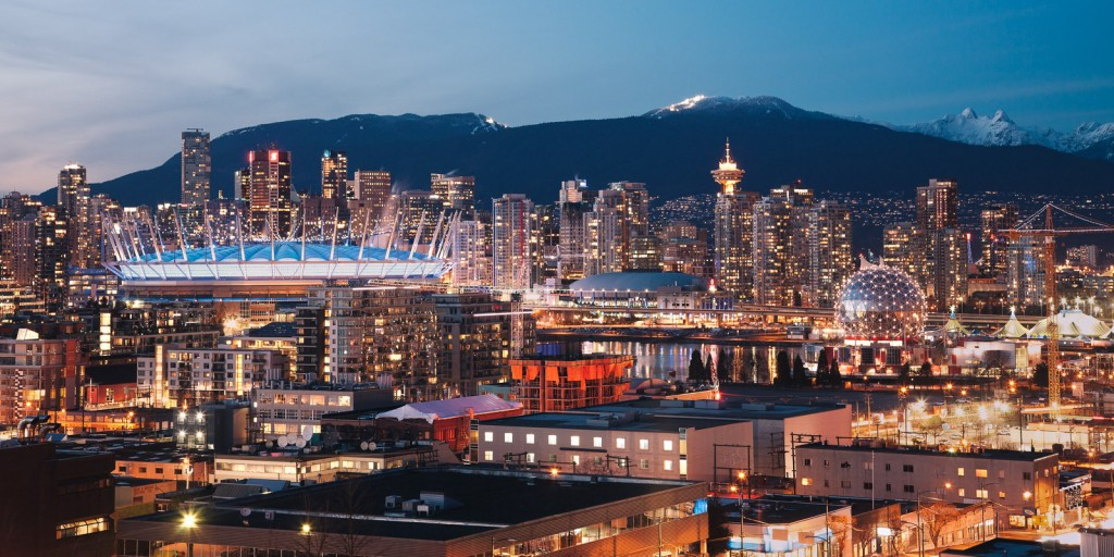 This image shows a panorama of Vancouver's skyline at dusk. Mountains are visible in the backgorund.