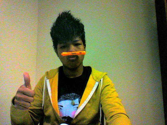 A picture of me balancing an orange highlighter between my nose and lips. I'm giving a thumbs up. I am evidently very tired - how did I think that hair was okay? Ugh.