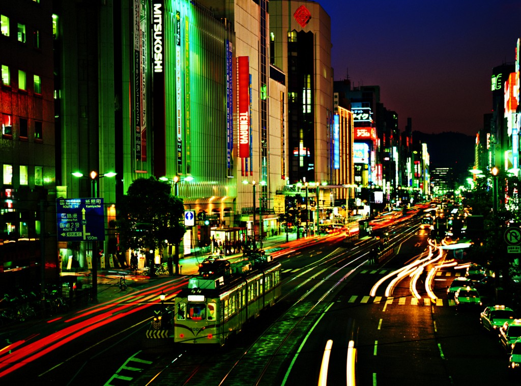 This image shows a scene of Hiroshima at night. Tall buildings line a concrete street. Cars and a streetcar can be seen on the street.