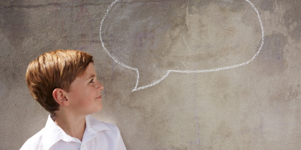 Boy with chalk speech bubble on wall