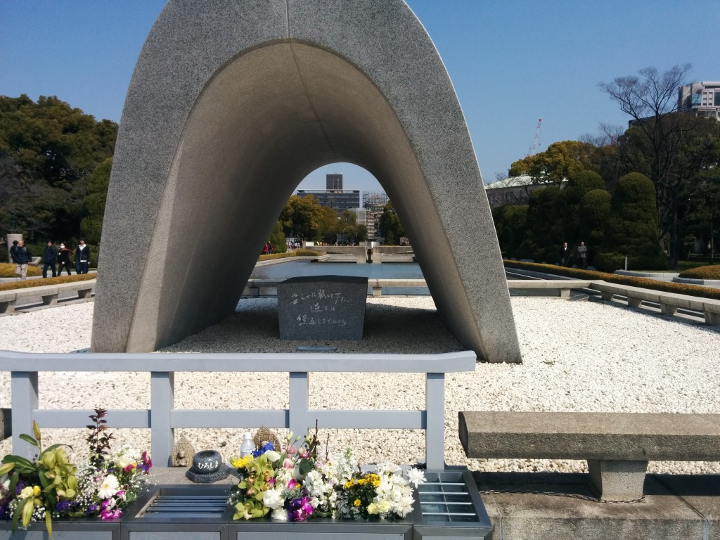 This image shows a concrete arch situated on a bed of pebbles. Flowers can be seen in the immediate foreground, in front of the bed of pebbles. Trees are visible in the background.