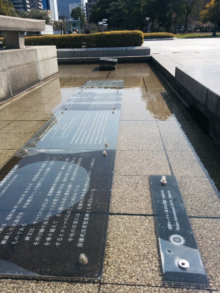 This image shows a signboards submerged in shallow water. It is at the Peace Memorial Park in Hiroshima. Trees are visible in the background.