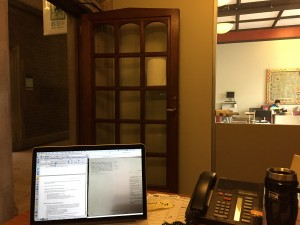 A quaint little office with a big Hart House wooden door, a window looking into the Map Room, an old-school telephone, my coffee, and my laptop with what looks like Russian homework in progress.