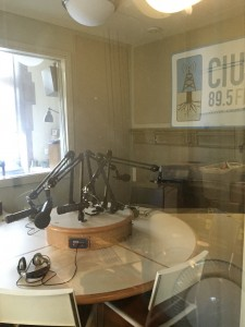 A side view of the on-air booth for CIUT 89.5 FM in the Map Room, with all the microphones, gadgets, and even the big fancy fireplace