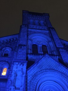 Looking up from the base of the big centre tower of University College, lit up in blue, looking spectacular