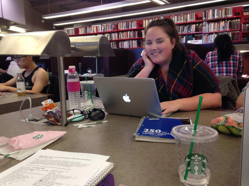 a table at robarts is shown with laptops and books on it, a girl in the background smiles at the camera from behind her laptop