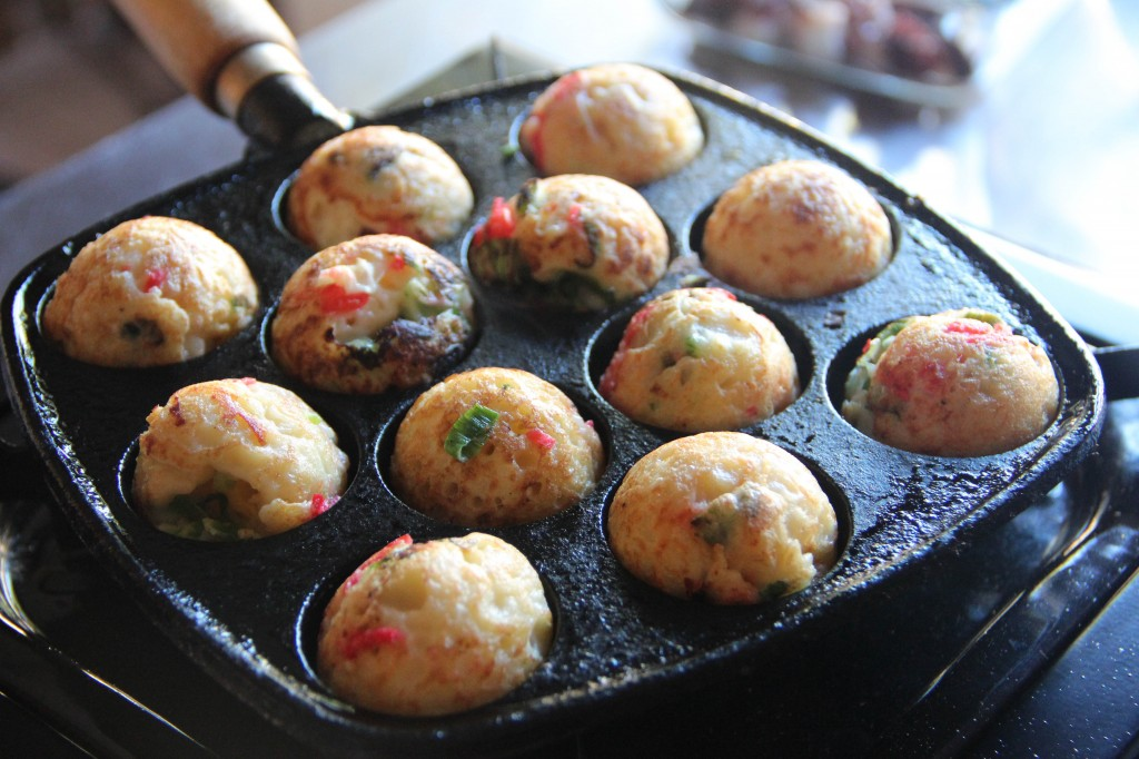 This image shows twelve takoyaki balls being cooked in a metal pan.