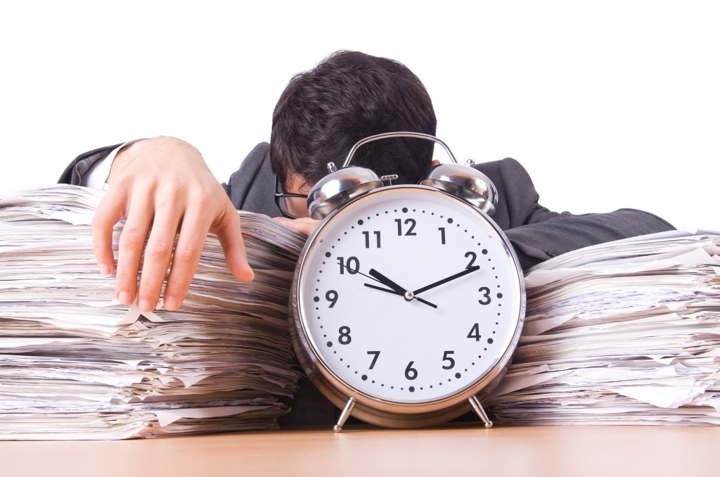 Man sleeping on a stack of papers, as a clock maliciously continues ticking on nearby
