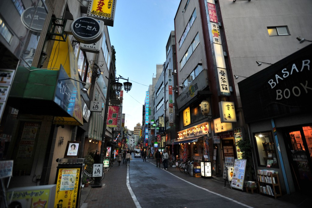 This image shows a narrow street lined with buildings featuring neon-signs.