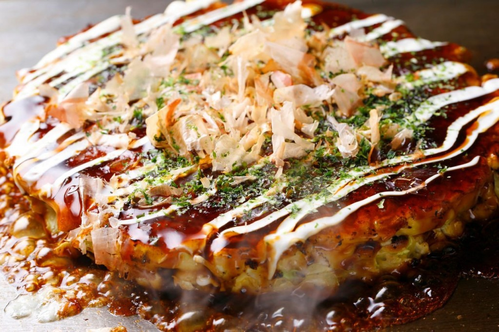 This image shows an okonomiyaki grilling on a teppan. It is topped with a brown sauce, mayonnaise, bonito flakes, and a green garnish.