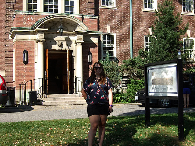 "a girl stands in front of a red brick building and smiles. beside her is a sign that says ""st. hilda's"""