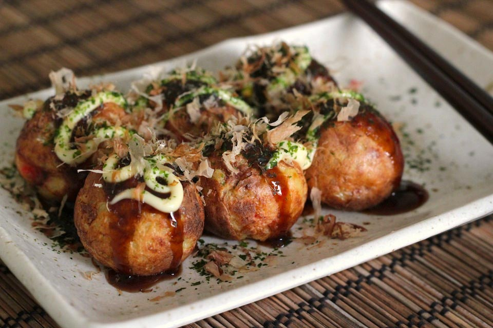 This image shows six takoyaki balls presented neatly on a white dish. They are topped with Bonito flakes, mayonnaise, and a green garnish.