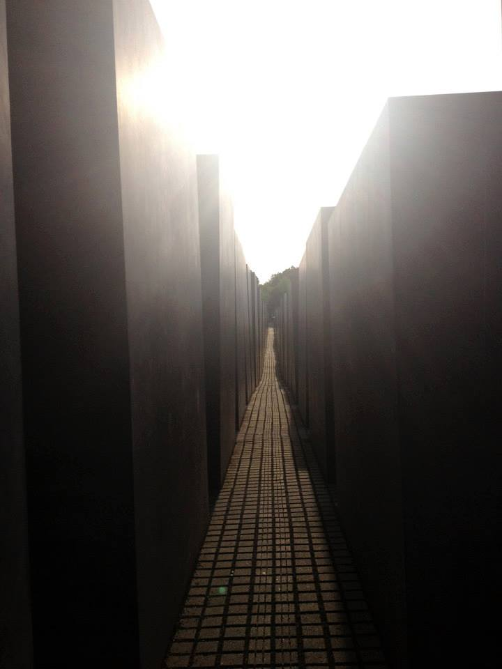 Inside the Berlin Holocaust Memorial, a narrow alley between rows of concrete slabs with the bright sun shining at the top.