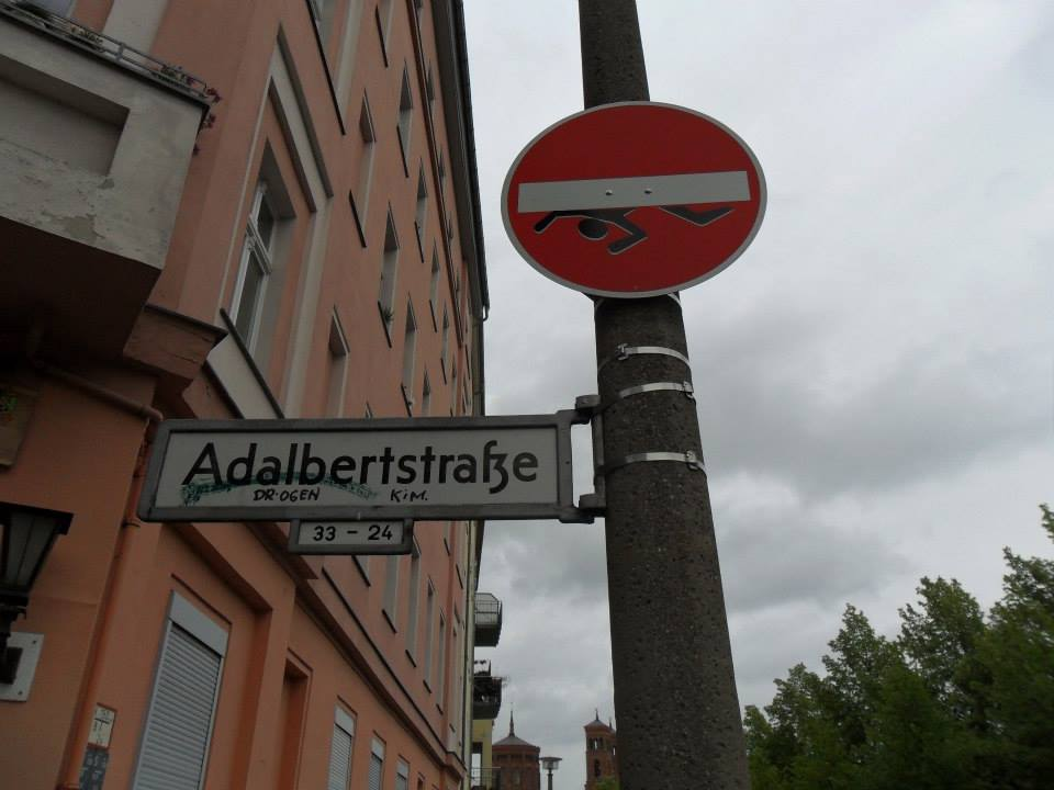 "The street sign for the location of my Berlin apartment, Adalbertstrasse (Adalbert Street). It's covered in graffiti and the red  ""do not enter"" sign has a sticker of a little stick figure being crushed by the white line."