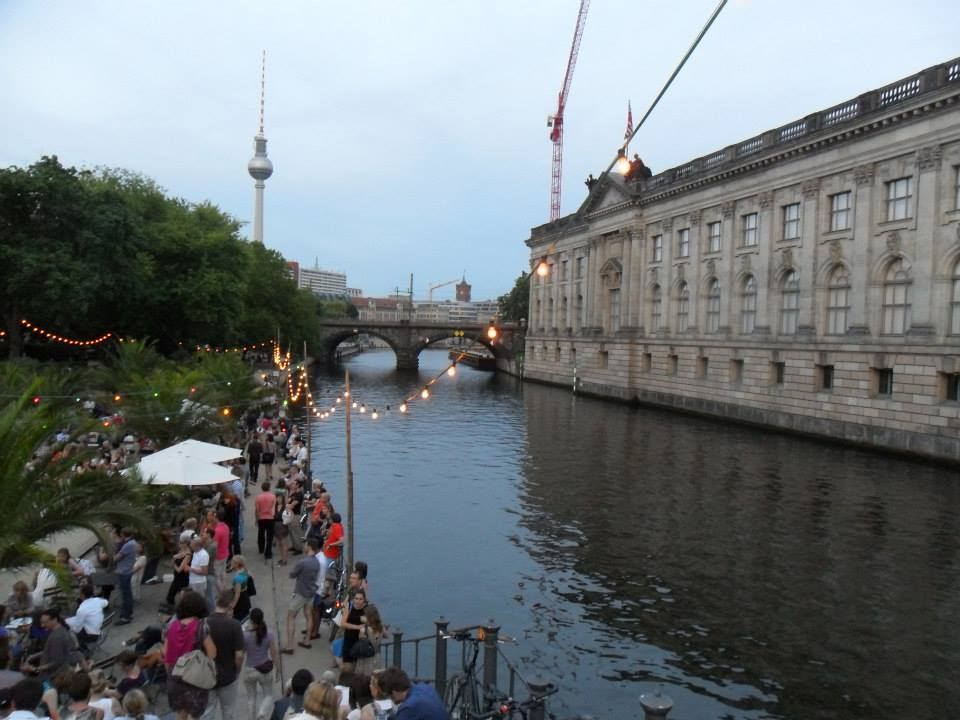 A scene in Berlin - people by a waterway, with an older building on the opposite side of the water, a string of lights along the edge, the TV tower in the background.