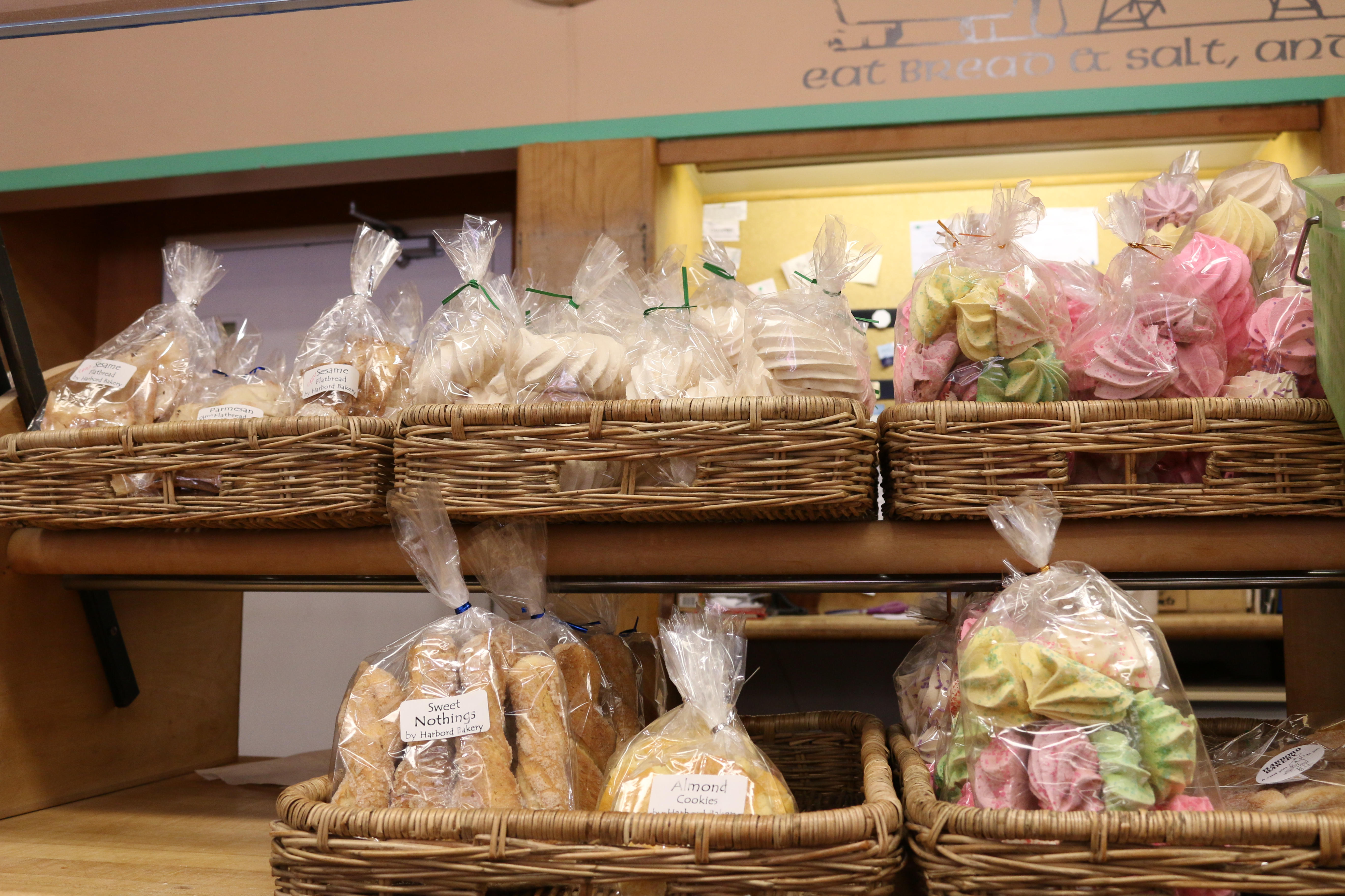 Packaged baked goods inside Harbord Bakery. Pictured are sweet nothings, almond cookies, and meringues in plastic bags inside wicker storage boxes.