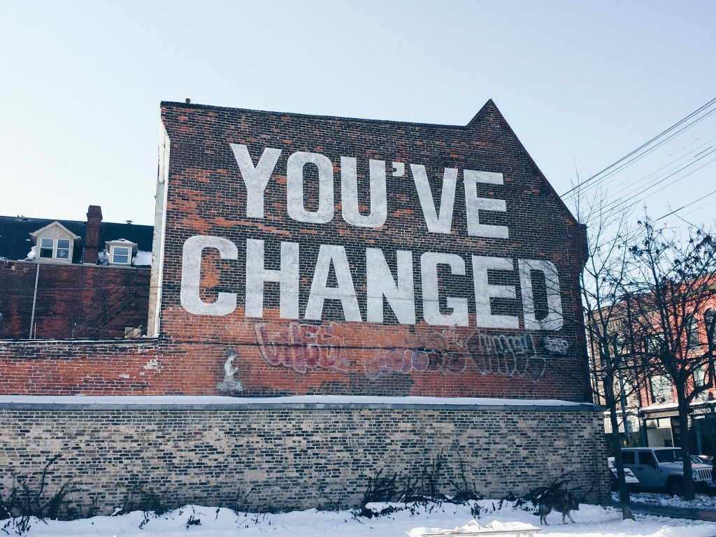 "A brick wall with a mural of big block letters and the words ""You've Changed."""