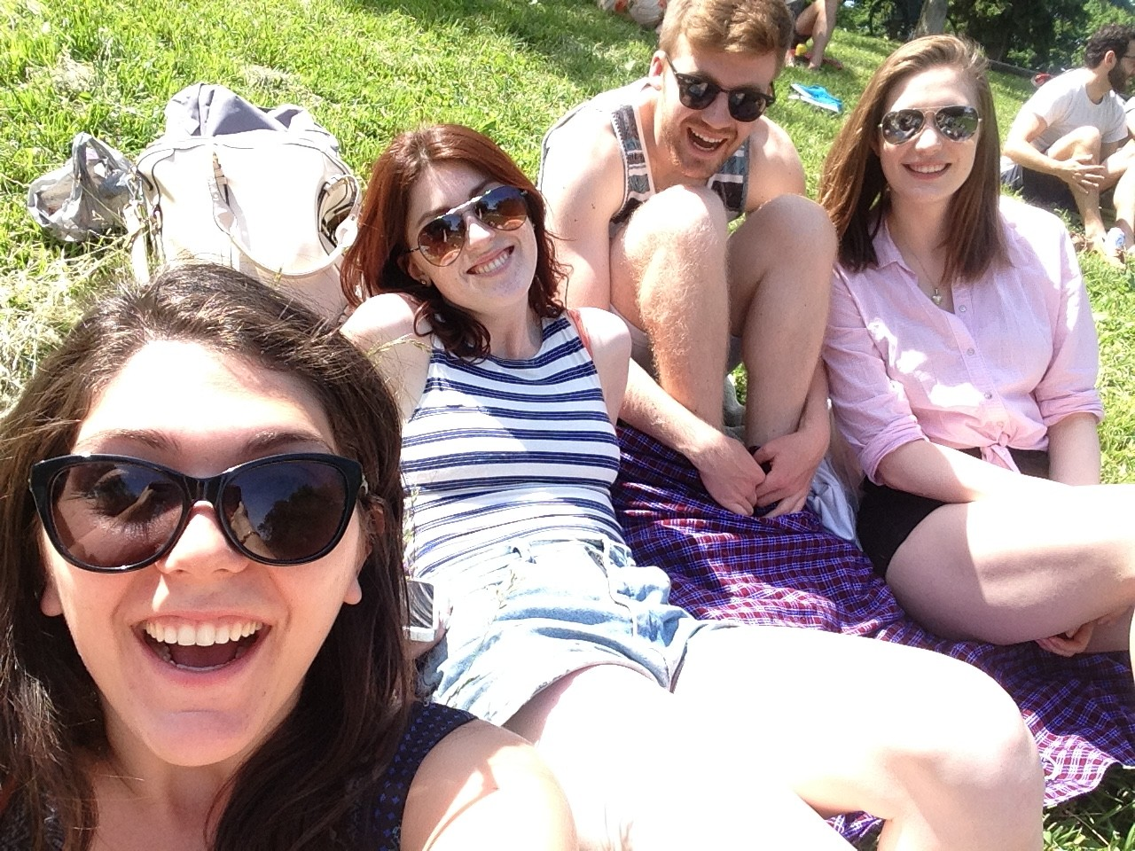 A selfie of me and three friends hanging out in Trinity Bellwoods park.