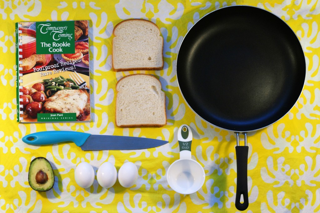 photo of cook book, frying pan, bread, eggs, avacado, and cooking utensils